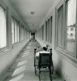 A leprosy patient wheels down a hallway.