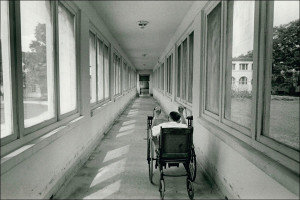 A leprosy patient wheels down a hallway. Photo: Mark Petty.