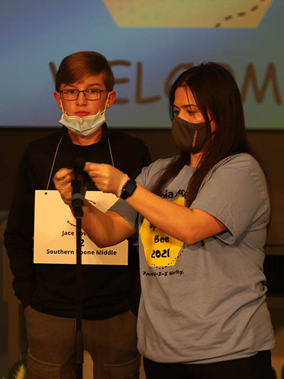 Jace Bowman of Southern Boone Middle School prepares for his turn at the Scripps Regional Spelling Bee while MU student Emina Catic provides some instructions.